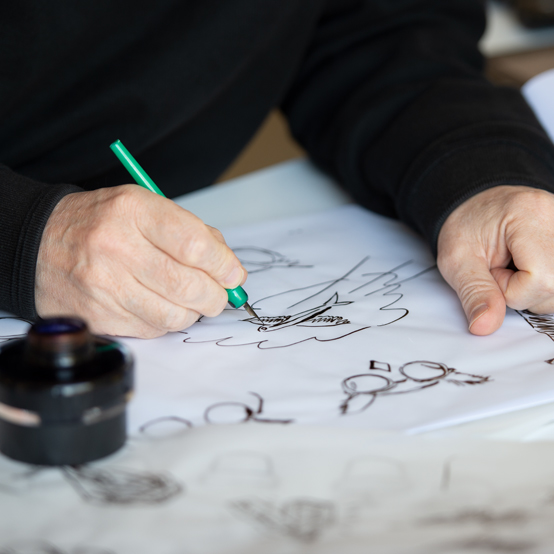 Tim Grey drawing Morgan's brand illustrations with pen and ink